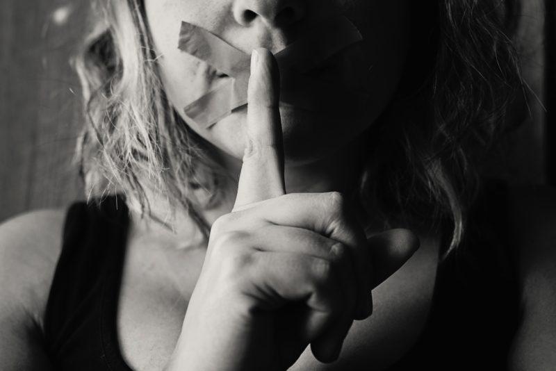 femme qui met doigt devant sa bouche