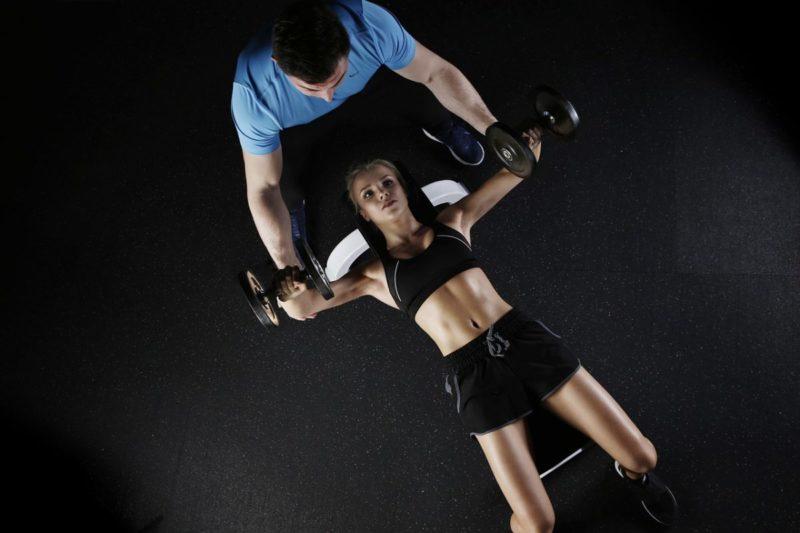 coach sportif aidant une femme à soulever des poids
