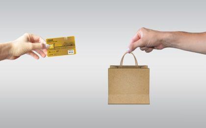 main venant de la gauche de l'écran tend une carte bancaire à une autre main avec un paquet qui sort de la droite de l'écran