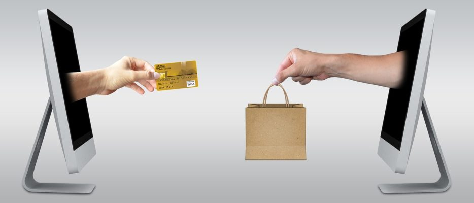 main traversant un écran d'ordinateur avec une carte bancaire contre une autre main avec un produit